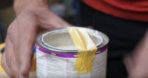 Wie auf dem Bild gezeigt, klebst du zwei Streifen Kreppband mittig über die Farbdose. Damit verklebt dir die Farbdose nie wieder.