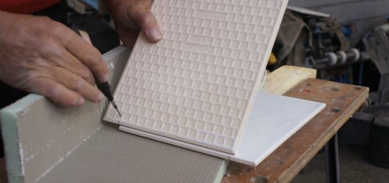 Die Fliese, die zugeschnitten werden soll haltest du parallel zur bereits eingelegten Fliese und zeichnest das kurze Ende mit einem Bleistift an.