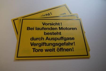 Schild – Vorsicht! Bei laufenden Motoren besteht…